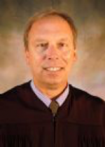 man smiling in judge's robes